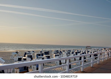 "Westerland beach with its famous blue and white ""Strandkörben"" at sunset"