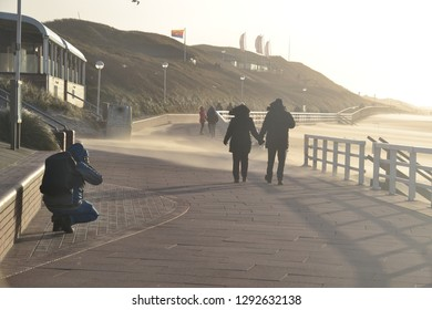Westerland, Sylt / Germany - January 1st 2019: heavy winds on the island Sylt on New Year's Day. Sand brushes over the pier from the beach as people are bracing the winds