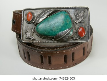 Western antique turquoise and red stones mounted on a gray metal eagles and feather background on a brown belt.