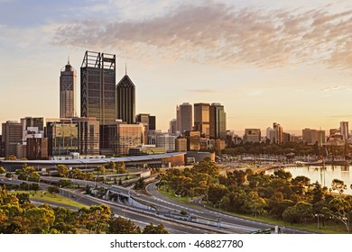 Western Australia capital city Perth at sunrise during golden hour. Bright warm sun light sheds on skyscrapers and city-line.