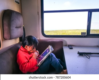 Western Australia - September 2, 2017 : Little girl is playing gadget inside the motor homes while travelling in Australia.