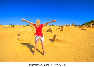 Western Australia travel freedom concept. Carefree woman with open arms watching the desert of Pinnacles limestone in Nambung National Park of Cervantes, in WA state of Australia