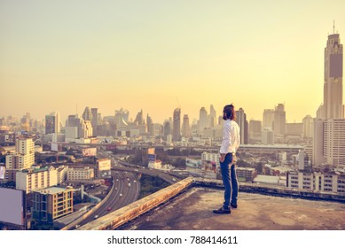 Western businessman looking at the city at sunset on a rooftop
