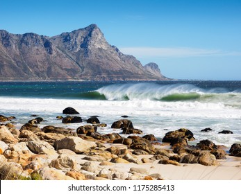 Western Cape beach. False Bay on a windy day. A rocky beach, and a single wave breaking on a windy day. Hottentot's Holland mountain across the sea.