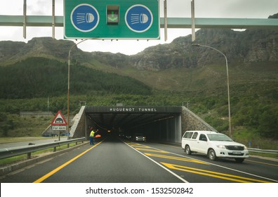 Western Cape, South Africa - July 25, 2019:  approaching the entrance to the Huguenot tunnel on the N1 national road with oncoming cars or vehicles and a green sign indicating to switch on headlights