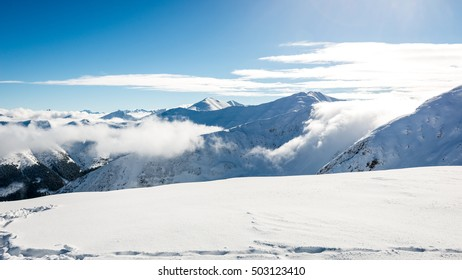 western carpathian mountain tops in winter covered in snow with bright sun and blue sky. slovakia