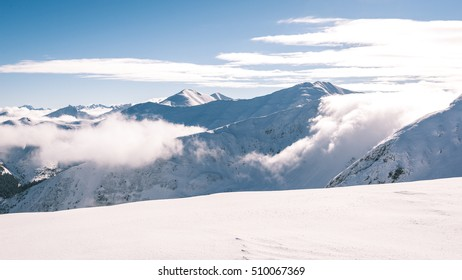 western carpathian mountain tops in winter covered in snow with bright sun and blue sky. slovakia - vintage film look