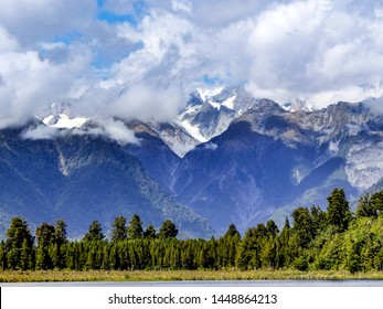 Western coast New Zealand mountains scenic view. Lake Matheson, Mount Cook, Mount Tasman, snow capped and cloud capped mountains.