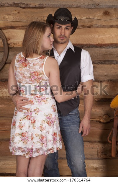 A western couple is standing in front of a wooden background.