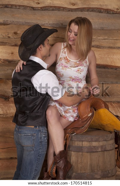 A western couple is talking while she is sitting on a saddle.