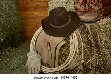 Western Cowboy hat with cowboy boots, leather gloves, leather chaps and a roper's rope on hay in a barn