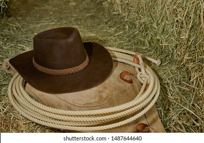 Western Cowboy hat with leather chaps and a roper's rope on hay in a barn