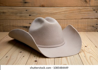 Western cowboy hat made of fur on wooden background.