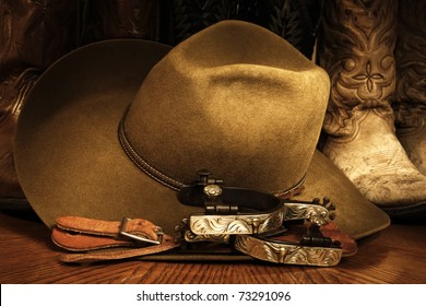 Western or cowboy themed image of a cowboy hat, fancy spurs, spur leathers and cowboy boots arranged on a wood grained surface with lighting accents.
