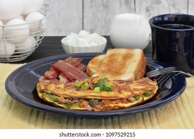 A Western or Denver Omelet breakfast with toast and bacon.  Close up with selective focus on omelet.