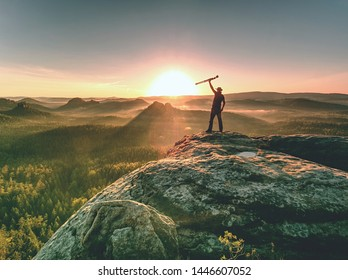 Western fashion photographer set tripod and camera. Hiker with cowboy hat will takes pictures of dreamy foggy mountains landscape and sunset in blue sky background.