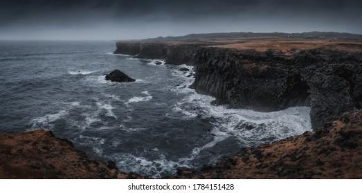 Western Iceland nature landscape, panorama view. Basalt rock cliff in Snaefellsnes (Snæfellsnes) peninsula near Arnarstapi village. Stormy waves at rainy weather
