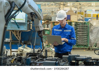 Western man, caucasian, an engineer or worker use laptop notebook computer device to control smart robot welding hand system automate manufacturing machine engine in factory, industry. People