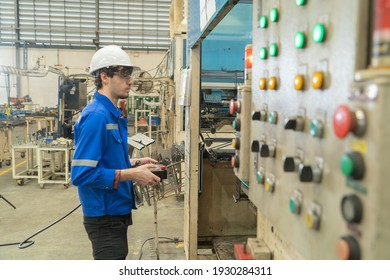 Western man, caucasian, an engineer or worker control the smart robot welding hand system automated manufacturing machine engine in factory, industry equipment in operation warehouse. People.