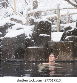 Western man soaking in Japanese Onsen or Hot Spring bath in traditional Ryokan hotel setting during Winter Snow, Japan.