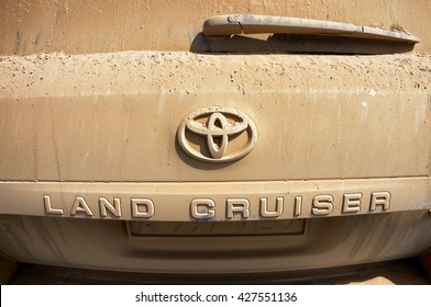 WESTERN MONGOLIA, MONGOLIA - AUG 5, 2011: Rear car with logo of Toyota and Land Cruiser full of dust traveling in Mongolian desert