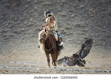 Western Mongolia, Hunting With Golden Eagle. Young Mongolian Girl - Hunter On Horseback Participating In The Golden Eagle Festival. Ancient Form Of Hunting In The Territory Of Kazakhstan And Mongolia