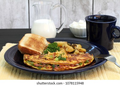 Western Omelet, with toast and home fries in a breakfast setting.  Selective focus on front top of omelet.