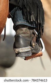 Western riding boots dirty in the neckline in the stirrup with spurs in color