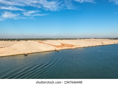The western side of Suez Canal. Foreground - construction site. In the background - railway, buildings and palm trees. View from the water, Suez Canal, Egypt.