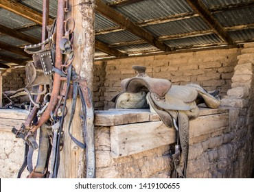 Western Style Bridle And Saddle. Interior of barn with worn and cracked leather riding saddle and a group of horse bridles.