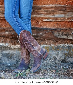 Western style image of cowgirl's legs in jeans and boots on deserted wall background
