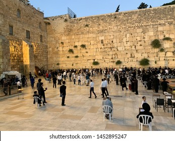 Western Wall, Jerusalem, Israel / June 18, 2019: Wailing Wall, or Kotel, known in Islam as the Buraq, is an ancient limestone wall in the Old City of Jerusalem. People praying.