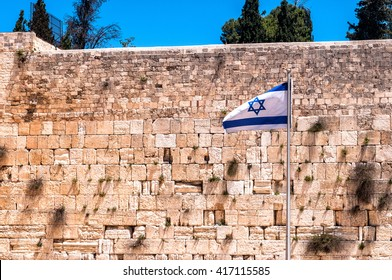 The Western wall in Jerusalem with state flag of Israel.