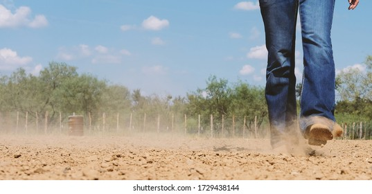Western wear shows person with cowboy boots and jeans kicking up dust from arena, blurred background with copy space on sky.