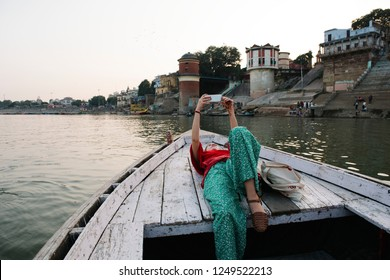 Western woman lying on a boat taking selfies in Varanasi