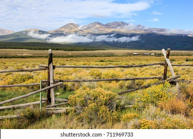 A western wooden cattle fence outside of Buena Vista, Colorado fences in a large yellow wild grass field containing cattle, a farmhouse, and wooden barn. Low clouds sit below the Collegiate Peaks.