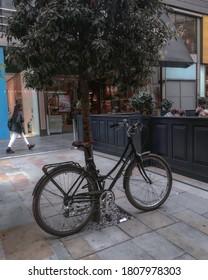 Westfield, Stratford, London, United Kingdom, 2016.  Woman walking by a bike in London.