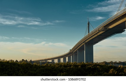 Westgate bridge in Melbourne on a beautiful, slightly cloudy morning, lit by the golden Australian sun.