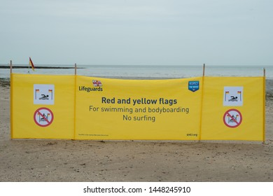 Westgate on Sea, Kent, UK - July 9 2019: RNLI Lifeguards Respect the Water banner on display, no surfing at this beach, flags on display.