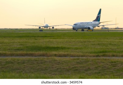 Westjet aircraft taxiing at YVR international airport on a summer night