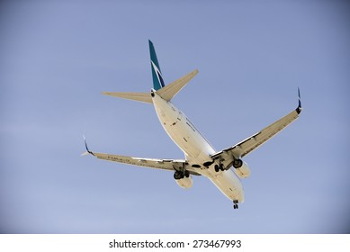 WESTJET AIRLINES - MAY 31, 2014: Boeing 737-800 with two jet engines is photographed before landing in Vancouver, YVR. The owner, Canadian compay WestJet Airlines was founded in 1996. British Columbia