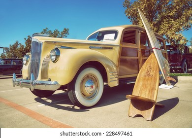 WESTLAKE, TEXAS - OCTOBER 18, 2014: A yellow 1941 Packard 110, wood bodied station wagon, is on display at the 4th Annual Westlake Classic Car Show. Front side view. Vintage style effects.
