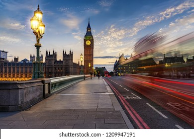 The Westminster Bridge and Big Ben clocktower by the Thames river in London after sunset with blurred traffic, United Kingdom