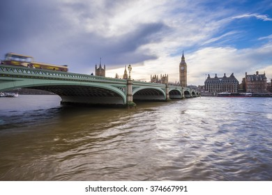 Westminster Bridge, Big Ben and Houses of Parliament with sightseeing bus at sunset - London, UK