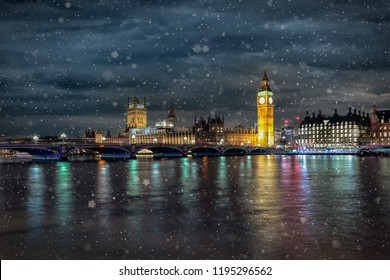 Westminster Bridge, the Parliament and the Big Ben in London on a cold winter night with falling snow, United Kingdom