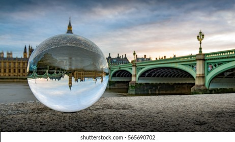Westminster and Westminster Bridge seen through a crystal ball on a cloudy evening in London, United Kingdom