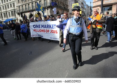 Westminster, London. 27 March, 2017 A female police officer supervises a pro-EU rally march towards Westminster held as part of a campaign against Brexit and leaving the EU..