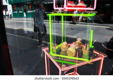 Westminster, London, England - August 6 2011 : Cake shop display of male torso cupcakes for sale sitting on pink and green neon Perspex shelves with the reflection of a pedestrian in the glass, Soho