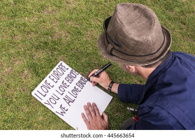 """Westminster, London, UK - 25 June 2016: Man writing """"I love Europe"""" on a poster as part of protests against Brexit in front of the House of Parliament in London, UK."""