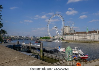 Westminster, London, UK - June 8, 2018: Westminster Pier with cruisuer boat.  Shows the London Eye and County Hall in the background set againsta blue sky.